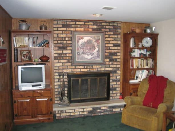 traditional family room design with floor to ceiling brick fireplace with wooden shelves on left and right sides