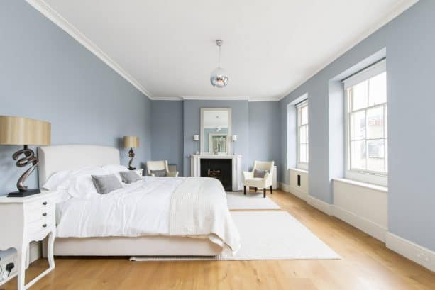 a grey and white bedroom with light hardwood floor