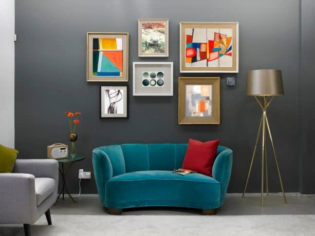 grey and blue contemporary living room with red cushion and warm-toned wall arts