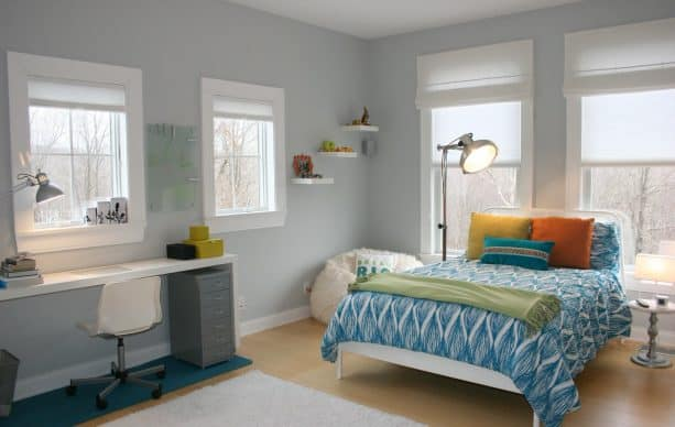 a cool blue and grey bedroom with warm-colored accent pillows