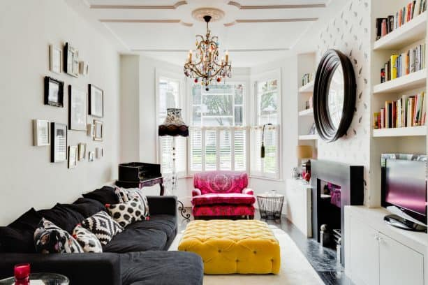 a living room with charcoal grey sectional couch and mustard yellow tufted upholstered table