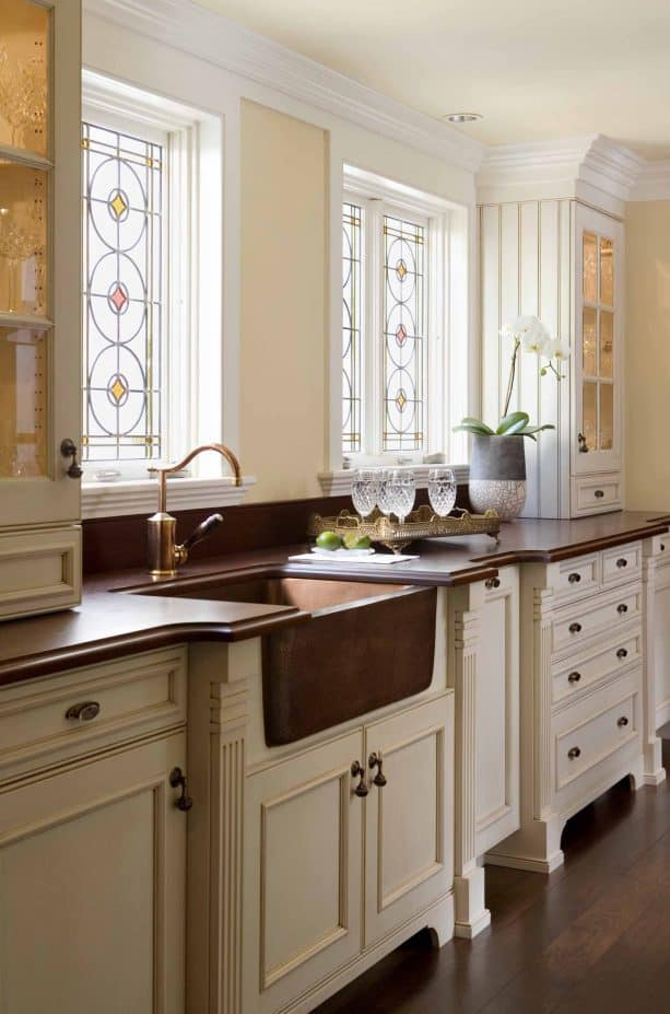 off-white cabinets paired with dark wood countertops and copper sink