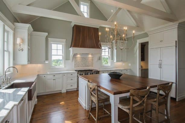 off-white kitchen cabinets paired with copper range hood and sink