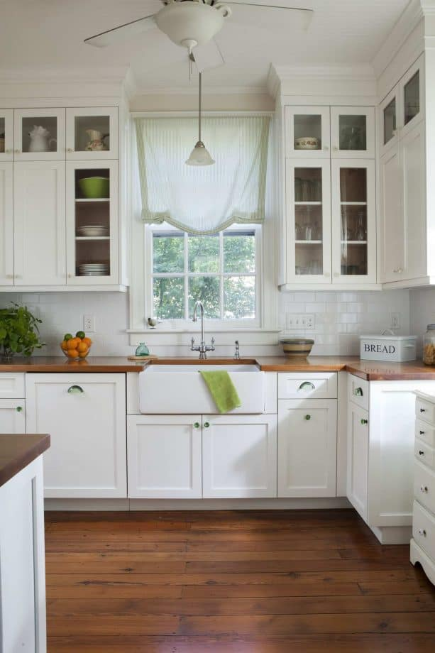 white shaker kitchen cabinets with solid white sink and wooden countertops