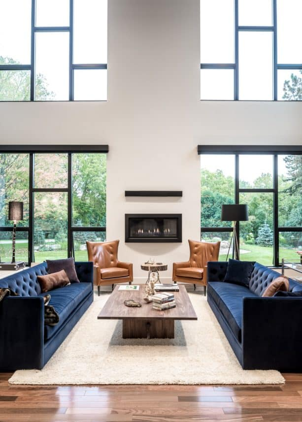 a family room with navy blue sofas and beige rug