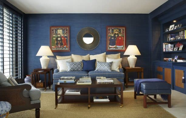 living room with navy blue grasscloth walls, navy blue cabinets, soft blue sofa, beige cushions, and beige flooring