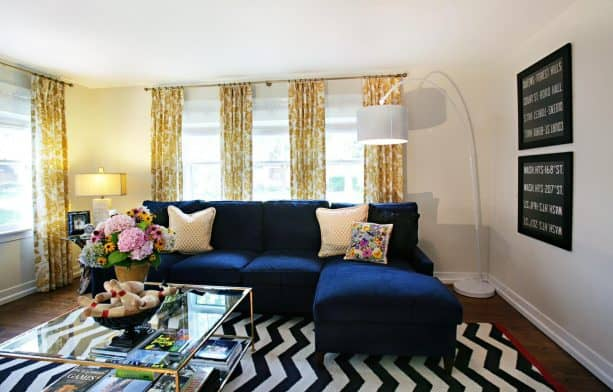 living room with navy blue sectional couch and yellow drapes