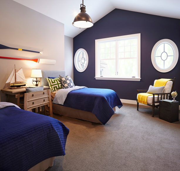 navy blue-dominated bedroom with bright yellow throw blanket