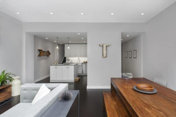 open-style living dining room with light grey wall and dark brown hardwood floor