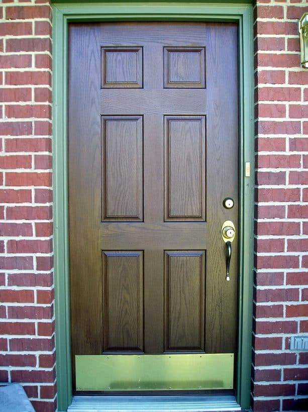 a brown-stained front door with fern green trim