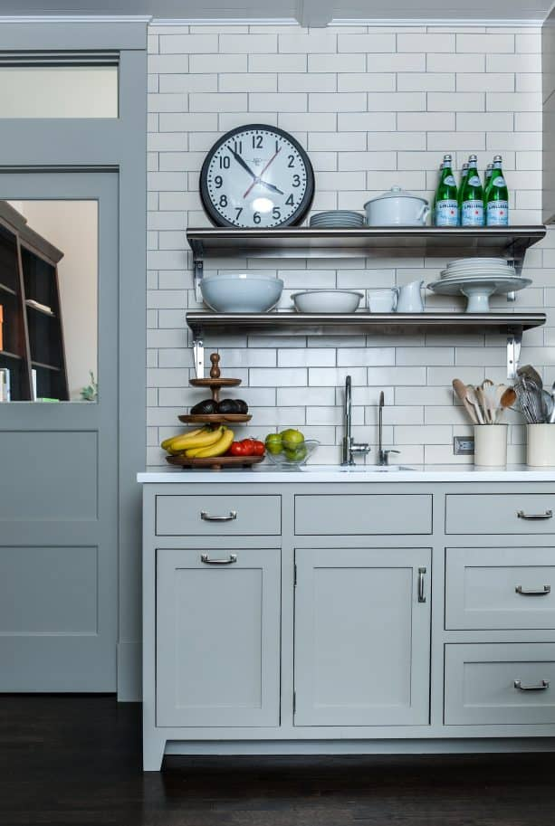 wall-size kitchen backsplash with white subway-style tile and grey grout