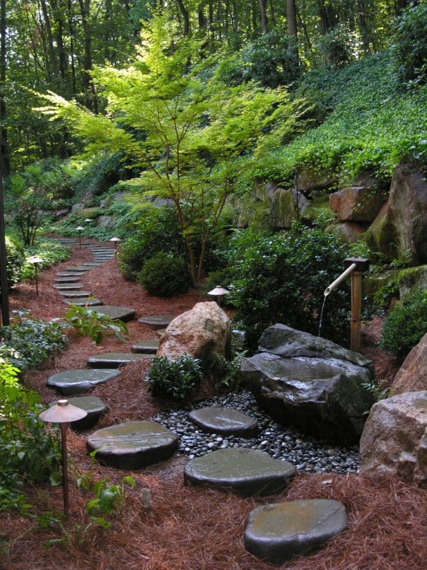 an amazing traditional landscape with real bluestone stepping stones and pine needles mulch
