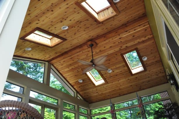 a traditional porch with the combination of glass panels and T&G ceiling from stained cedar material