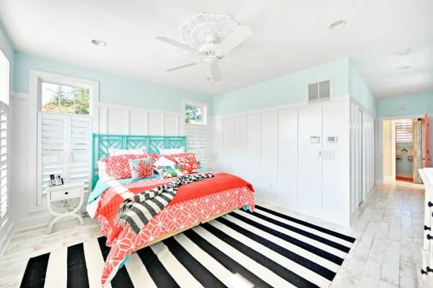 a turquoise bed with bedding sets in coral tones