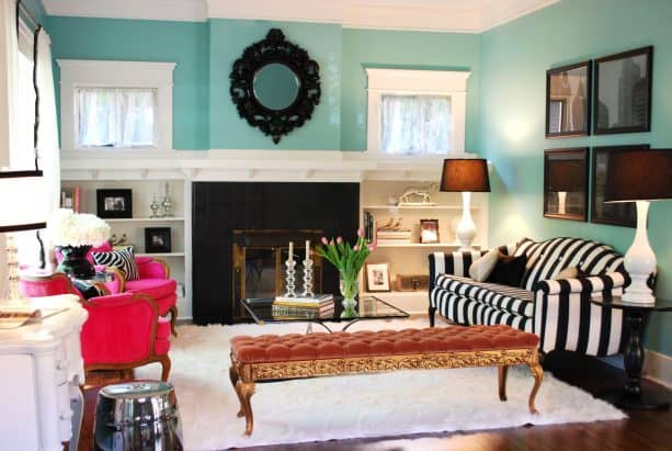 an eclectic living room with turquoise walls and black accents