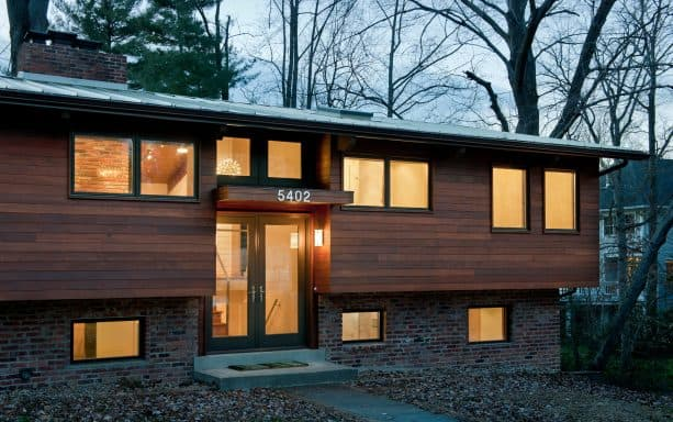 the remodeled house looks contemporary with new entry cover, black window and door frame, and horizontal wood wall cladding