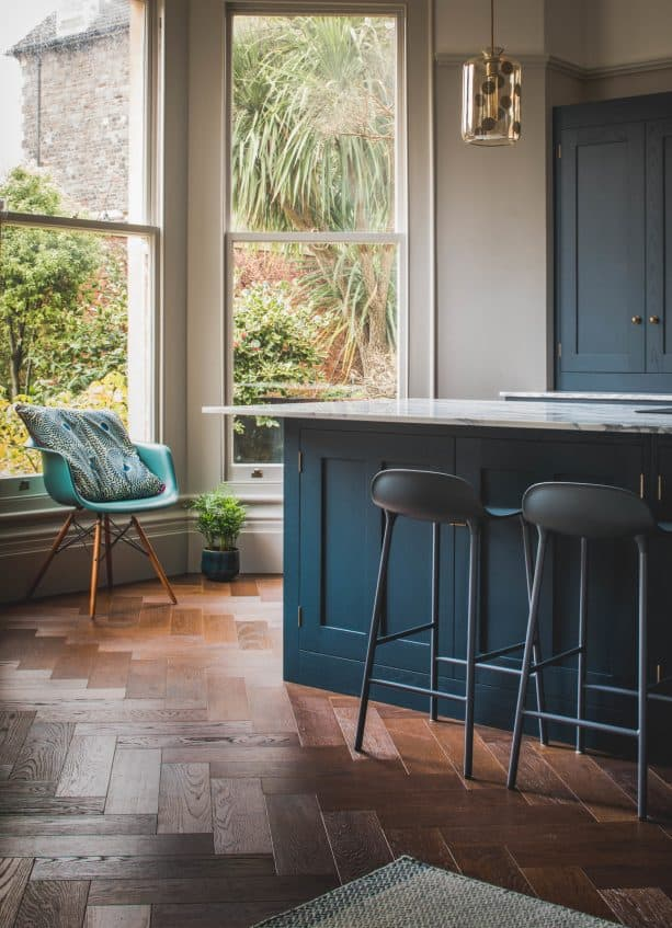 turquoise chair and dark blue island in a contemporary kitchen