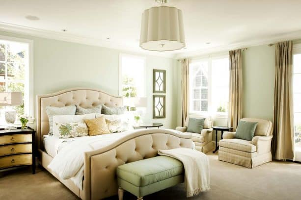 a traditional bedroom with tan and pale green color scheme