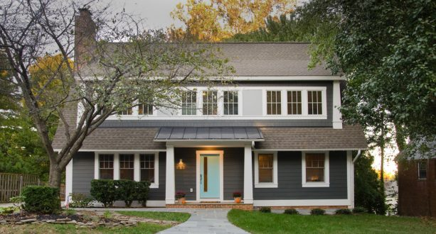 a craftsman exterior with dark grey color, white trim, and soft blue door