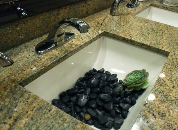 a modern white undermount sink with black river rocks decoration