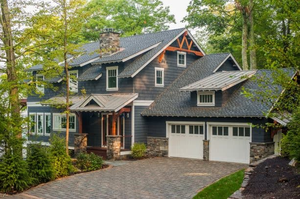 a rustic house with dark grey siding and white exterior trim