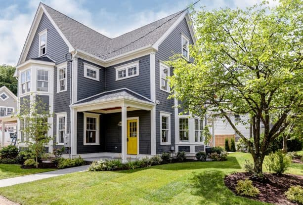 a transitional home exterior with dark grey paint, white trim, and yellow front door