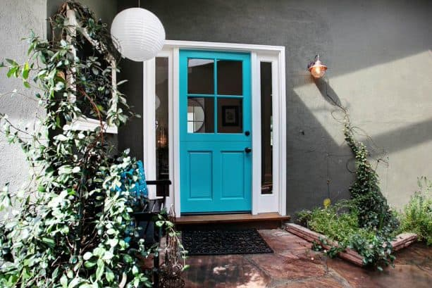 dark grey wall, white trim, and bright blue door for a colorful look