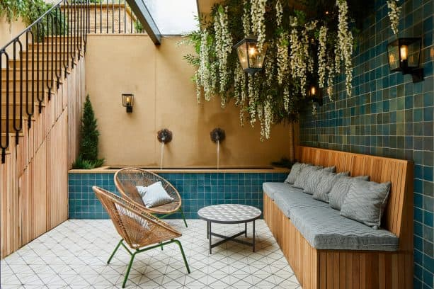 Mediterranean walkout basement patio with blue tiles, hanging plants, and water feature