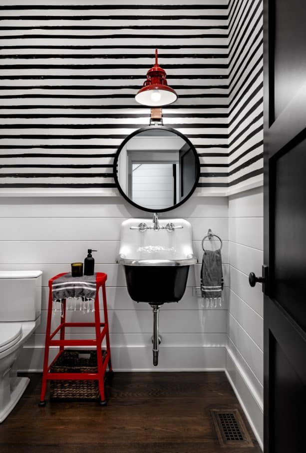 a black and white modern farmhouse bathroom with accentuating red stool