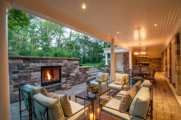 a covered walkout basement patio with fireplace, living area, dining table set, and a small kitchen