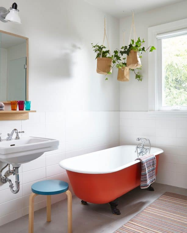 a red tub with black feet in a Scandinavian bathroom