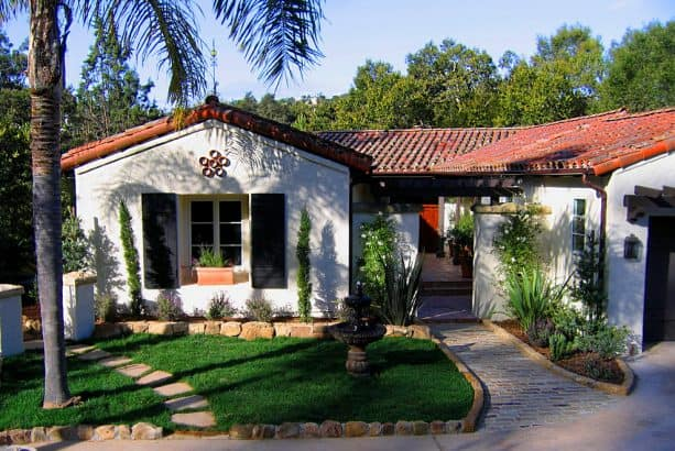 a mediterranean home exterior with white wall, black shutters, and red clay roof tiles