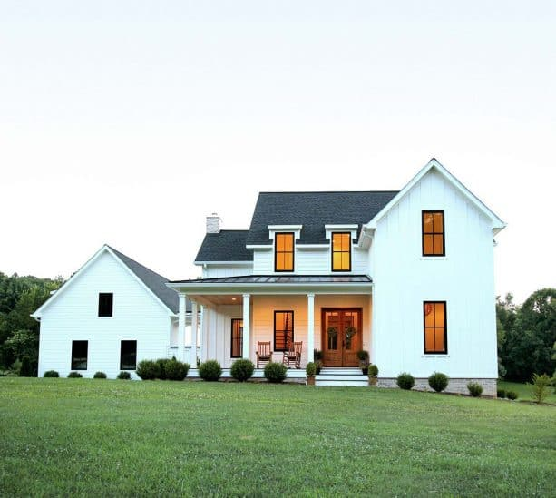 a white farmhouse with charcoal grey roof shingles