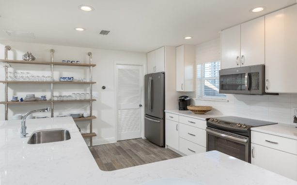 slate appliances and white cabinets in a white beach-style kitchen