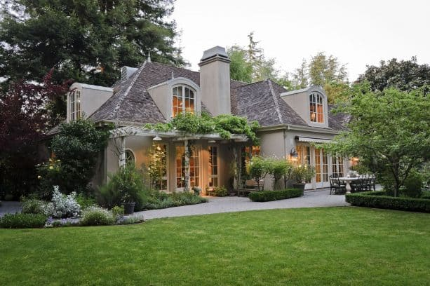 a French country exterior with tan stucco and off-white trim