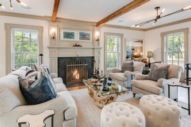 a farmhouse living room with white walls, greige trim, and greige fireplace