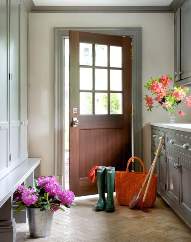 a traditional entry with off-white walls, grey trim, and wood door