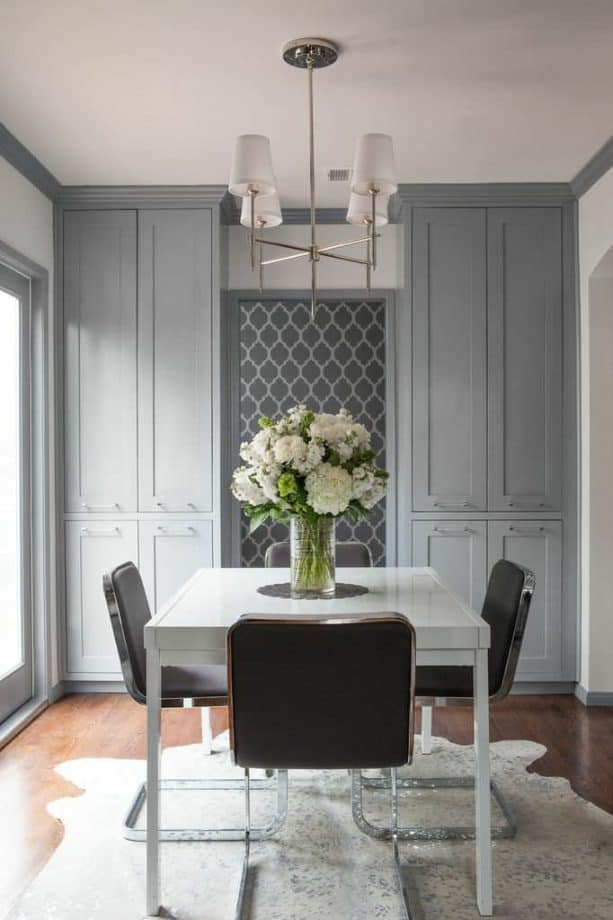 a transitional dining room with white walls, grey trim, and grey custom built-in cabinets