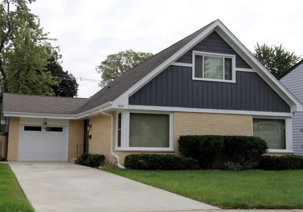 an L-shaped ranch home exterior with cream-painted brick and grey siding combo