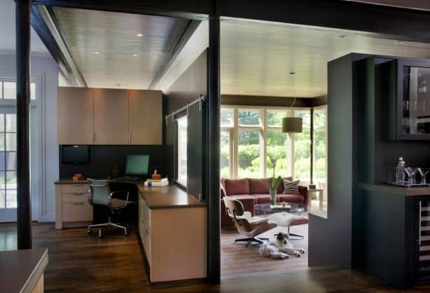 a glassless window with black sliding closures as a part of a partition in a contemporary interior