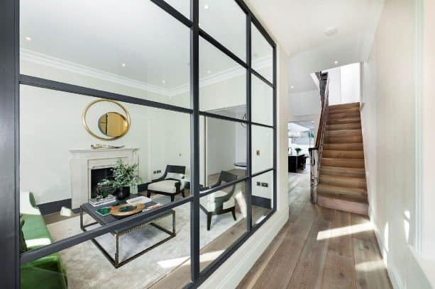 a large glass interior window separating a hallway and a living room