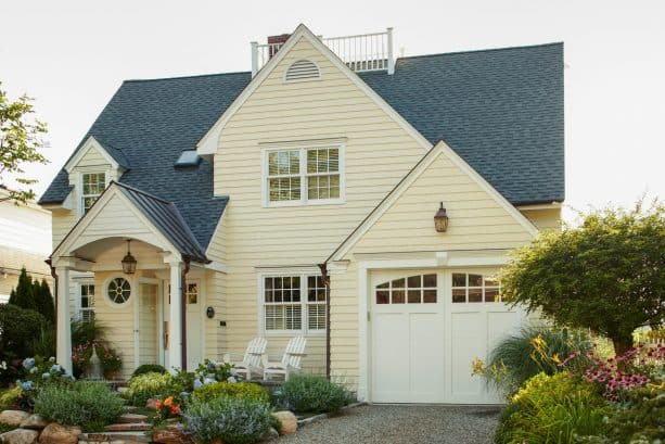 a traditional exterior with buttercream yellow siding, charcoal black roof, and white for the doors, windows, and trim