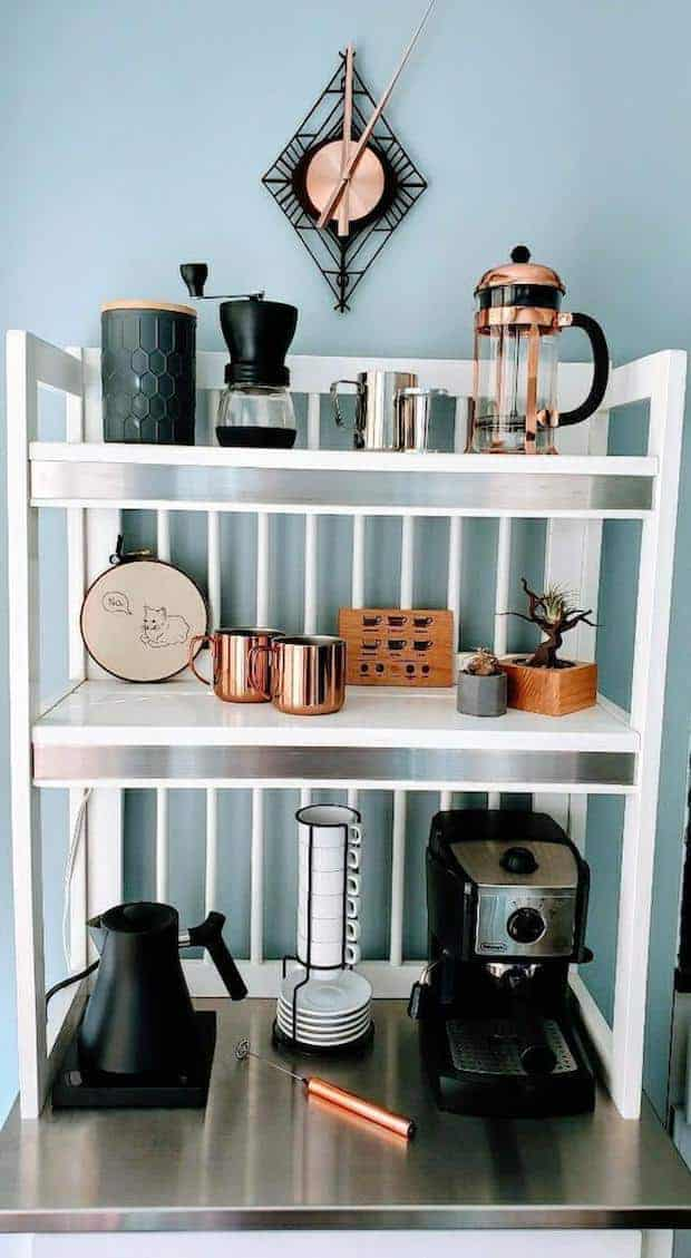 Coffee station with a counter and several shelves stocked with items