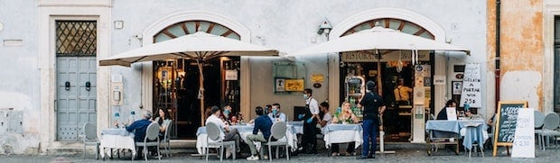 Patrons sitting at a sidewalk cafe in Rome