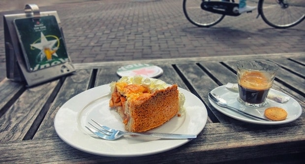 coffee and pastry on a table with a bike passing by in the background