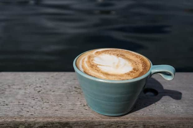 coffee on a ledge that looks like a cappuccino or a latte