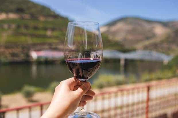 A hand holds up a glass of red wine in front of a lake