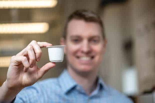 Dr. Zac Hudson holds up a sustainable coffee pod made partly from bamboo.