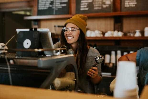 A smiling female barista behind an espresso machine in a coffee shop