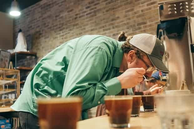 A coffee taster hunched over a row of coffee cups